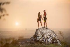 站立在大石近的登山车的骑自行车者 库存照片