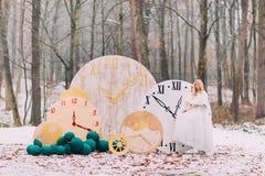 站立在大葡萄酒的美丽的白肤金发的新娘在秋天森林创造性的婚礼装饰计时 库存照片