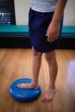 站立在大蓝色重音球的男孩的低部分 免版税库存图片