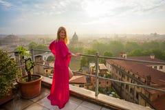 站立在大阳台和俯视的城市的妇女在清早 免版税库存照片