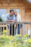 站立在大阳台微笑的愉快的夫妇 免版税库存照片