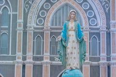 站立在天主教主教管区前面的保佑的圣母玛丽亚雕象有蓝天背景在尖竹汶府 免版税库存照片