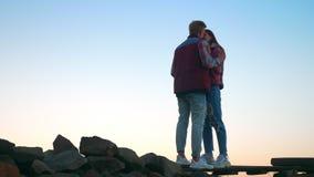 站立在天空背景的石头的夫妇地道射击,举行,真实的爱震动,令人惊讶的看法 股票录像