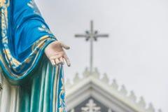 站立在天主教主教管区前面的保佑的圣母玛丽亚雕象的手 免版税库存照片