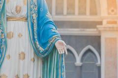 站立在天主教主教管区前面的保佑的圣母玛丽亚雕象的手 库存照片