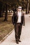 站立在太阳镜和皮夹克的一个公园的年轻英俊的人 免版税图库摄影