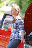 站立在失败的汽车旁边的担心的女性驾驶人 库存照片