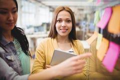 站立在女性工友附近的照片编辑程序指向在稠粘的笔记 免版税图库摄影