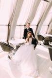 站立在她后的新娘坐椅子和新郎经典家庭画象在餐馆 免版税图库摄影