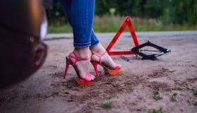 站立在她残破的汽车、警报信号三角和螺旋千斤顶,脚附近的妇女特写镜头 免版税库存图片