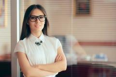 站立在她的办公室前面的别致的聪明的女商人 免版税库存图片