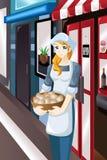 站立在她的商店前面的女性店主 免版税库存图片