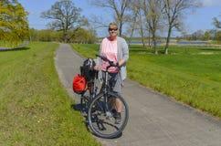 站立在她的在农村围拢的自行车附近的妇女在Lueneburg荒地的易北河 免版税图库摄影
