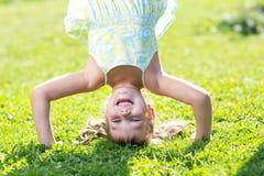 站立在她的在绿色草坪的头的愉快的小女孩 免版税库存照片