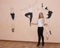 站立在她的在芭蕾姿态的脚趾的年轻舞蹈家与Pointe 免版税库存图片