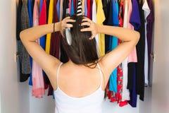 站立在她的壁橱前面的沮丧的妇女,设法发现某事佩带 免版税库存照片