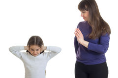 站立在她的妈妈旁边的小女孩和关闭耳朵手 免版税库存图片
