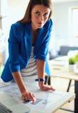 站立在她的工作场所附近的一个美丽的女商人的画象 免版税库存图片