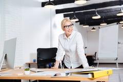 站立在她的工作场所附近的一名美丽的微笑的女实业家的画象 免版税库存图片