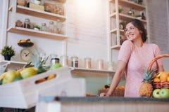 站立在她的果汁糕后柜台的美丽的妇女  图库摄影