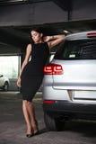 站立在她的汽车附近的黑礼服的美丽的少妇 免版税库存照片