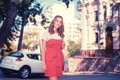 站立在她的花梢白色汽车附近的成功的兴旺的女实业家 免版税图库摄影