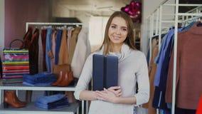 站立在她的衣物精品店,拿着片剂,微笑和看照相机的年轻女实业家画象 影视素材