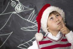 站立在委员会附近的小男孩 圣诞节帽子的男孩 免版税库存照片