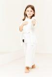 站立在姿态的空手道女孩佩带的和服 免版税库存图片