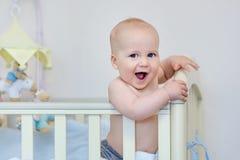 站立在婴孩床和笑上的小滑稽的男孩 微笑的阿多尔 免版税库存照片