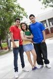 站立在学校前面的少年朋友 免版税库存照片