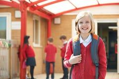 站立在学校操场的女孩佩带的制服 免版税库存图片