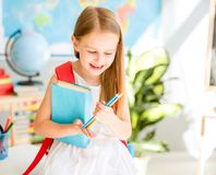 站立在学校教室的小微笑的白肤金发的女孩 免版税库存照片