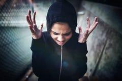 站立在学校校园的恼怒的十几岁的女孩 图库摄影