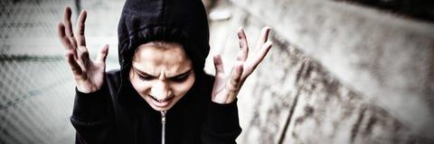 站立在学校校园的恼怒的十几岁的女孩 库存图片