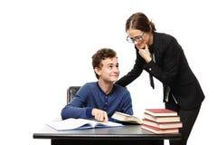 站立在学生的书桌和学生poi旁边的老师 免版税库存图片