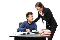 站立在学生的书桌和学生poi旁边的老师 库存照片