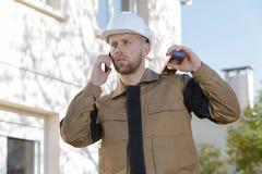 站立在安全帽打电话的建筑工地的建造者 图库摄影