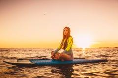 站立在安静的海的桨搭乘有温暖的夏天日落颜色的 免版税库存照片