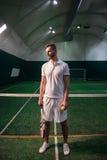 站立在室内法院的宜人的确信的网球员 免版税库存图片