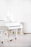 站立在宫殿大厅典雅的内部的白色大平台钢琴  免版税库存照片