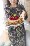 站立在家庭烹饪的厨房的愉快的少妇照片  在薄煎饼的焦点 库存图片
