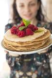 站立在家庭烹饪的厨房的愉快的少妇照片  在薄煎饼的焦点 免版税库存图片