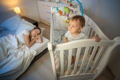 站立在小儿床和看疲乏的母亲Th的婴孩画象 免版税图库摄影