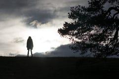 站立在小山上面的女性剪影  免版税库存照片