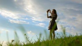 站立在小山和做与她的袖珍相机的黑礼服的美丽的深色的女孩照片 ame 库存照片