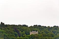 站立在小山的孑然豪宅在森林Erquy里 britte 库存图片