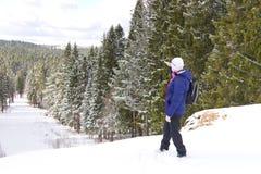 站立在小山顶部的中年女性旅客反对在远处也看冬天森林的背景 免版税库存图片