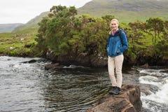 站立在小河的一个岩石的白肤金发的妇女 库存照片