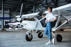 站立在小航空器附近的太阳镜的可爱的少妇 图库摄影